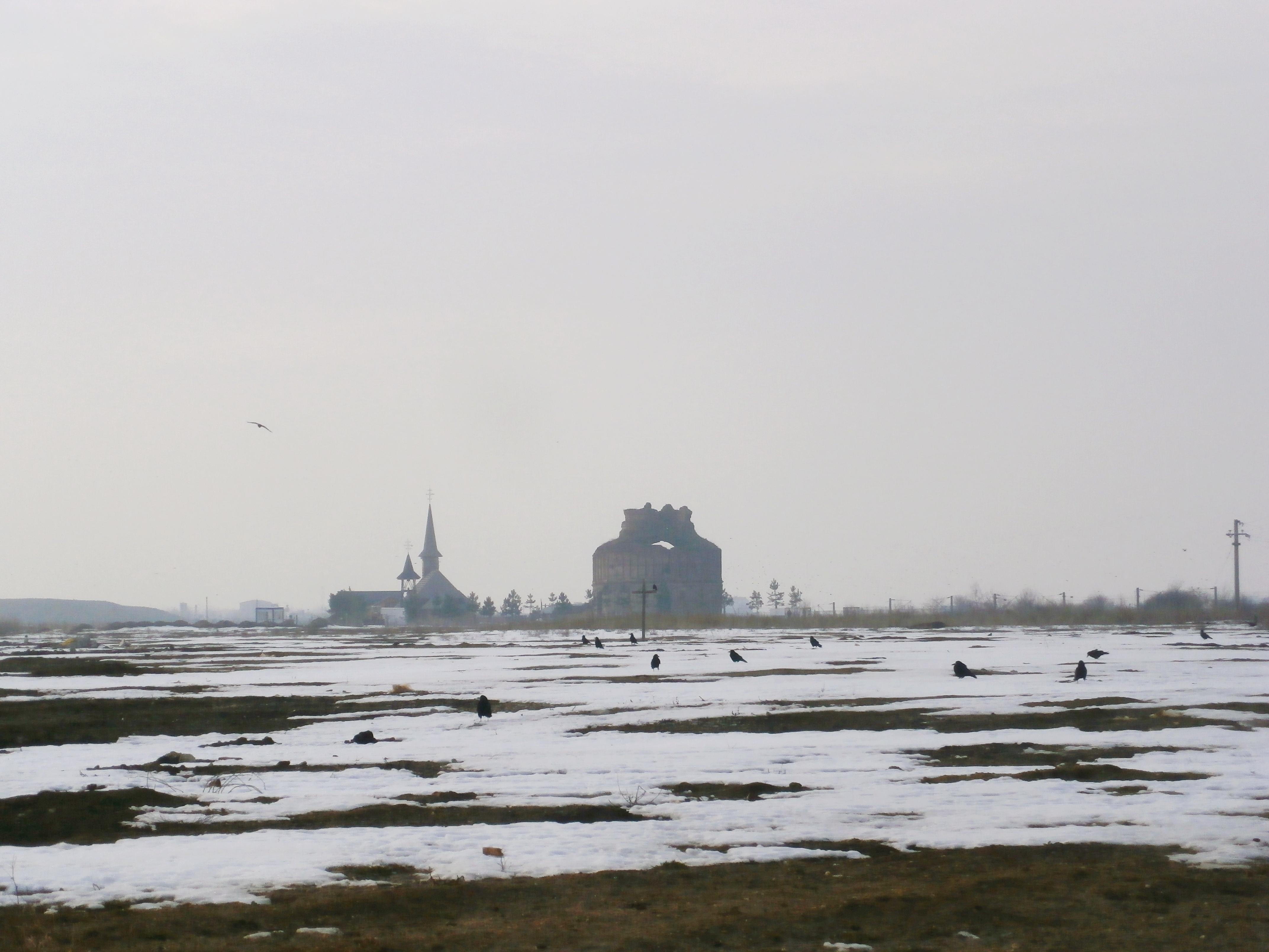 Înainte de a ajunge la ruine, exact în mijloc cămpului este situată o cruce.